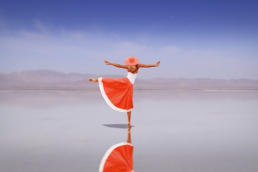 A woman in orange hat and dress dances like nobody's watching