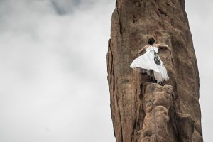 a woman in a long white dress climbs a cliff face