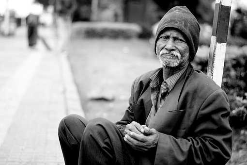 an old man begs on the street
