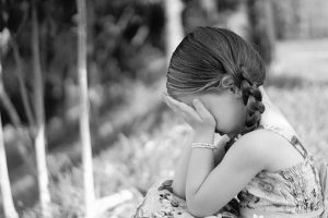 a little girl covers her face as she cries