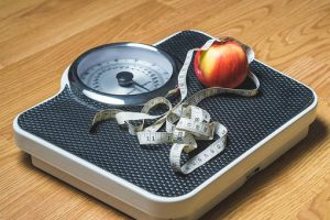 set of scales with a tape measure and an apple sitting on top