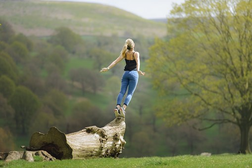 a woman stands on a ledge arms thrust back as she is about to take off and fly