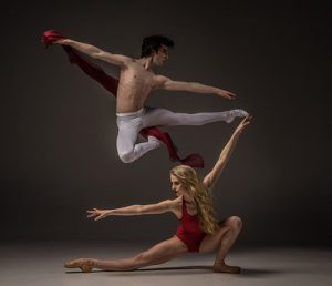 male and female ballerinas fly through the air