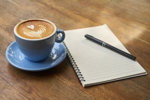 a nice fresh coffee sits on a table along with a pen and notepad