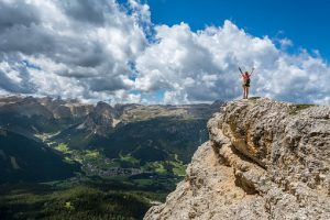 a man stands atop a mountain with a huge valley below raises his arms after conquering