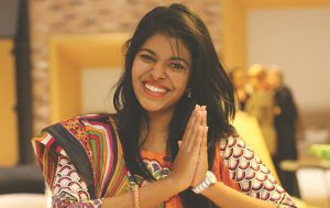 a girl with a huge smile offers praying hands saying namaste