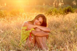 Beautiful girl in a yellow dress sits smiling in a field with suns rays on her back