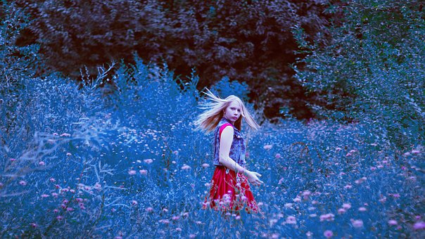 young girl in a field of native flowers looks back to look at the past she leaves behind
