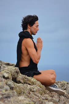 a man on a mountain top meditates and gives thanks