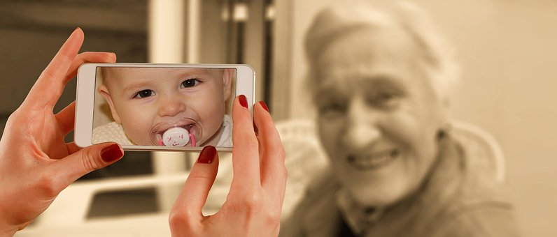 an old woman poses for photo but on the scree of the camera shows a photo of her when she was a baby