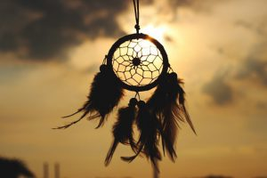 a dream catcher silhouettes the moon