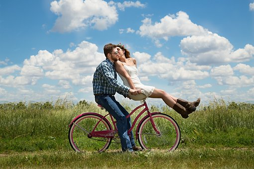 A man ao on a bicycle with his girlfriend riding on the handlebars stops and they kiss