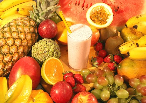 fruit shake ready to go surrounded by all the different fruit ingredients