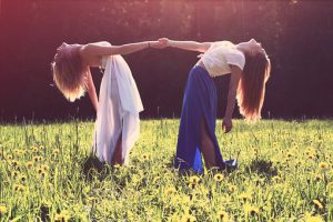 2 girls hold each others hand and lean back to look at the sky in a field of sunflowers