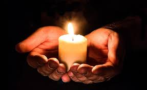 Hands clasped together offering a candle representing peace