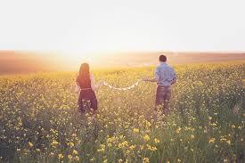 a man and a woman at sunset make a daisy chain in a field of daisys