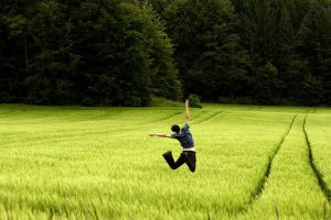 a man jumps for joy over a field of long grass
