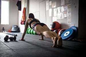 fit looking girl in the gym doing some pushups