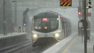A passenger train speeds past a station in heavy rain