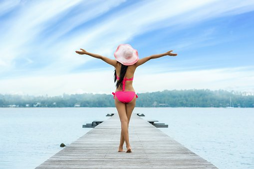 Picture of a lady in a pink hat and bikini walking out on the jetty ares raised in a classic carefree pose