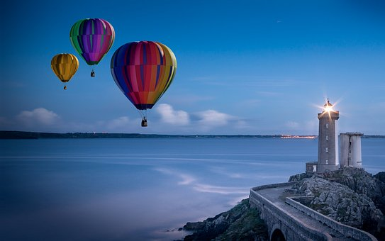 3 hot air balloons float passed a lighthouse over the ocean on dusk
