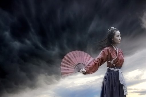 Chinese girls walks beyond the raging storm and opens her fan representing she is to leave the storms behind
