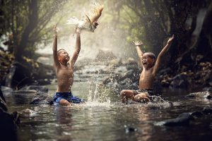 2 boys pay and swim in a creekand slpash water at a passing bird