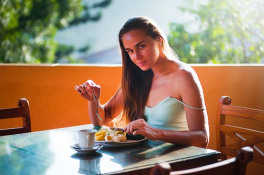 Beautiful confident young lady sits outdoors smiling and eating a nourishing breakfast the sun is shining and she has a beautiful view