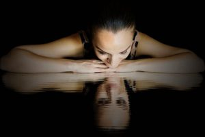 A lady lays above a reflection of herself smiling , knowing she can do this