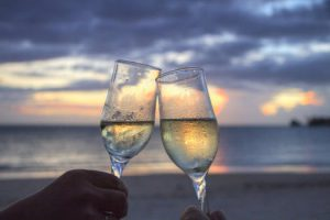 A sunset, a beach and two glasses of white wine come together