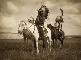 2 cherokee indians ride their horses in full indian attire