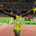 Usain Bolt raises his flag after winning another gold medal