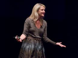 Mel Robbins in a grey dress and to speaks to her audience expressing herself with outstretched arms
