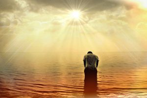 A Man stands knee deep in the ocean head bowed in gratitude the sun is setting and he is covered in it's rays of sunlight