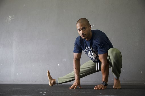 Fit looking man stares at camera while taking time to warm down and improve flexibility with a full body stretch