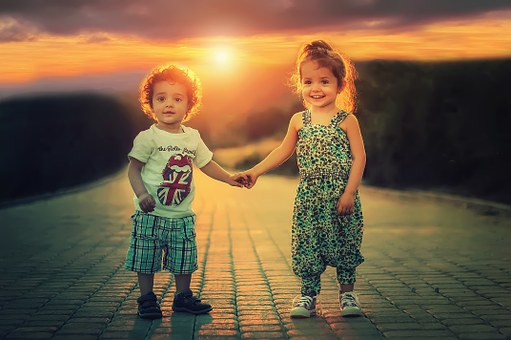 Brother and sister aged 2 and 3 holding hands with big smiles have no knowledge of fear as the sun sets behind them