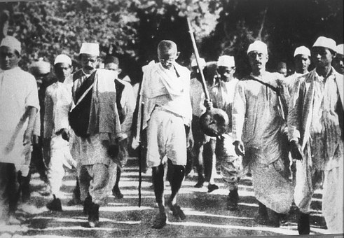 Black and white photo of Gandhi, head down surrounded by followers on his walk across India