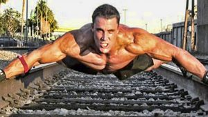 Photo of Greg Plitt no shirt doing pushups using two rail of a railway track