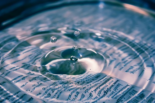 drop of water on a book of knowledge