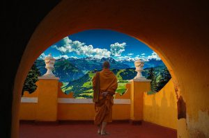 Buddhist looks out from his temple overlooking mountans and forests