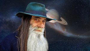 Old wizard with long black hair and a long white beard stands before Saturn in the background