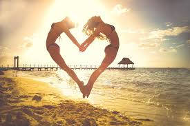 two woman at beach back to back holding hands leap in the air what separates the is the shape of a heart
