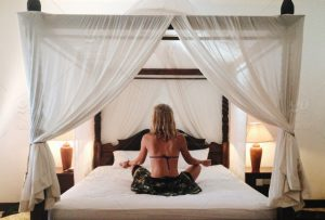 woman sits meditating on a beautiful white bed