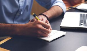 man sits with pen and paper at his desk planning his day for tomorrow