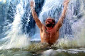 Man with a beard standing in waist deep water under a waterfall and jumps with glee with arms outstretched