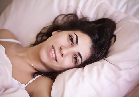 Woman laying on a bed looking fresh and relaxed after a good nights sleep