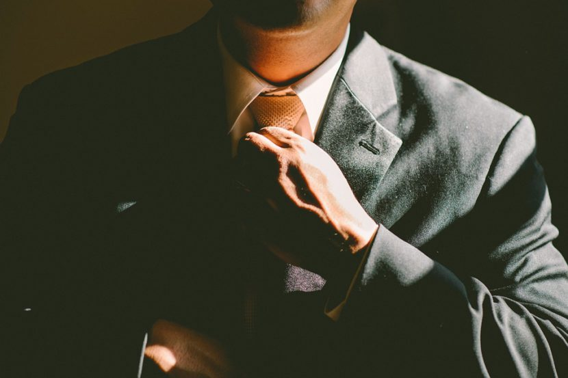 man in suit adjusts his tie