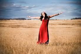 Girl in full length red dress stands in a field and looks to the heavens with arms outstretched expressing joy