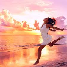 Beautiful pink sunrise a girl runs along the beach, arms out stretched in a typical expression of joy