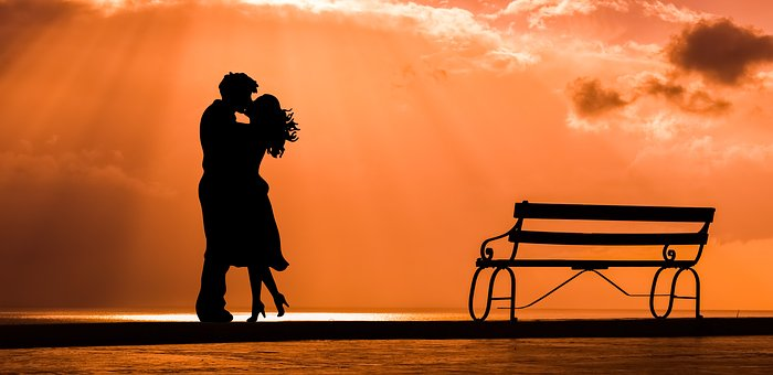 A sunset, the ocean,a park bench...In this moment two lovers embrace and kiss